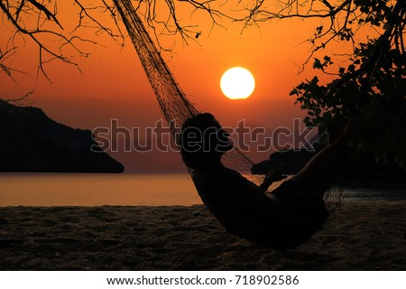 Silhouette of a woman relaxing on the beach with hammock, Red sky sunset background.