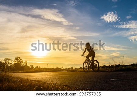 Silhouette of a woman rides a bike at sunset.Orange-blue sky background. #593757935