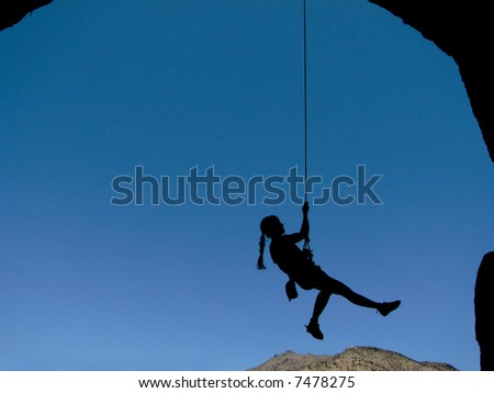 silhouette of a woman rock climber hanging by a rope