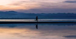 Silhouette of a woman running and dancing on the beach in the sunrise. Bayawan, Negros Oriental, Philippines