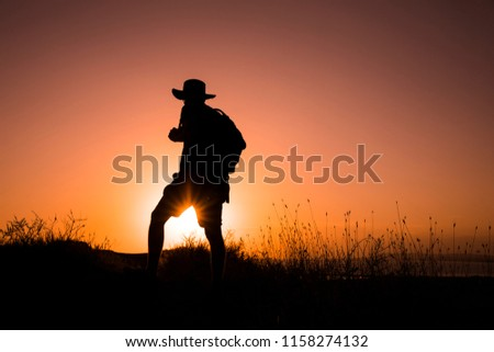 Silhouette of a woman with a backpack in the sunset.