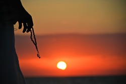 Silhouette of a woman with a rosary in the hands at sunset