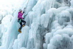 Silhouette of a woman with ice climbing equipment, axe and climbing rope, hiking at a frozen waterfall
