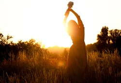 Silhouette of a woman with long natural hair in a long mustard-colored cotton dress picks wild flowers against the background of the sunset. Natural beauty, privacy in nature, women's day.
