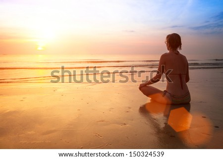 Silhouette of a woman yoga on sea sunset