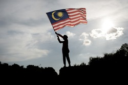 Silhouette of a young asian boy holding the malaysian flag celebrating the Malaysia independence day