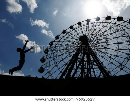Silhouette of a young boy jumping in excitement at a ferris wheel in an amusement park on a blue cloudy day.