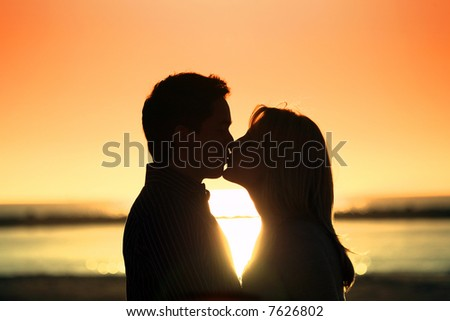 Silhouette of a young couple kissing at the beach with the sun setting behind them