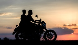 silhouette of a young couple man and woman on a motorcycle on sunset background