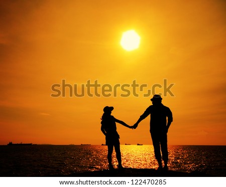 Silhouette of a young couple on sunset