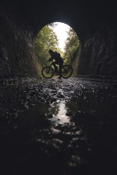 Silhouette of a young cyclist on a bicycle at the exit of a tunnel. Via verde de Loredo in Asturias, old railway tracks converted into a path. Silhouette of a person on a bicycle, sporty and active.