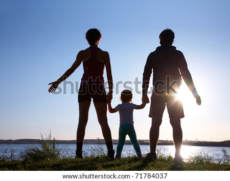 Silhouette of a young family with a child standing on a decline against the bright sun