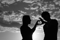 Silhouette of a young girl and her boyfriend with hearts made of fingers against the blue sky with clouds at sunset. Silhouette of the heart.Lovers in nature. Lovers silhouette. Black and white