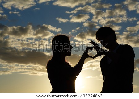 Silhouette of a young girl and her boyfriend with hearts made of fingers against the blue sky with clouds at sunset. Silhouette of the heart.Lovers in nature.Lovers silhouette. Happy guy and girl  #693224863