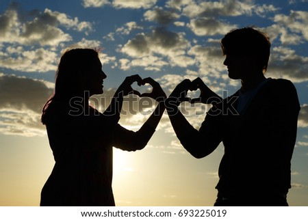 Silhouette of a young girl and her boyfriend with hearts made of fingers against the blue sky with clouds at sunset.  Silhouette of the heart.Lovers in nature.Lovers silhouette.Happy guy and girl    #693225019