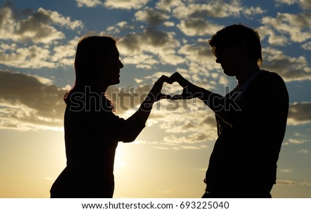 Silhouette of a young girl and her boyfriend with hearts made of fingers against the blue sky with clouds at sunset. Lovers in nature.Lovers silhouette. Silhouette of the heart #693225040