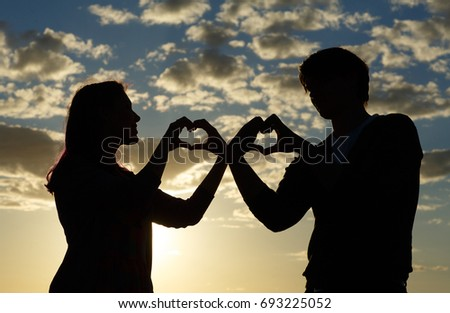 Silhouette of a young girl and her boyfriend with hearts made of fingers against the blue sky with clouds at sunset. Silhouette of the heart Lovers silhouette. Magic moments of loving hearts.  #693225052