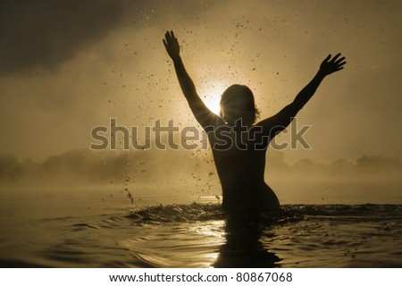Silhouette of a young girl with raised arms in the water