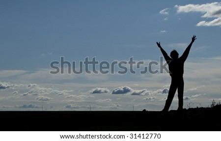 Silhouette of a young happy man on blue sky background