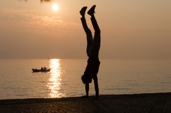 Silhouette of a young man handstanding in front of the sea at suset