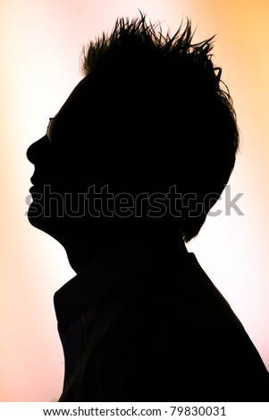 silhouette of a young  man in sunglasses  on white orange background - back-lighting