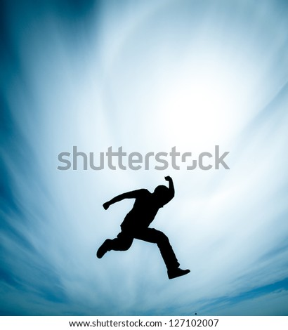 Silhouette of a young man jumping, shot against direct sun with lens flare, dramatic clouds background, saturated colors