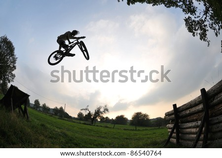 Silhouette of a young man performing a radical mountain bike jump