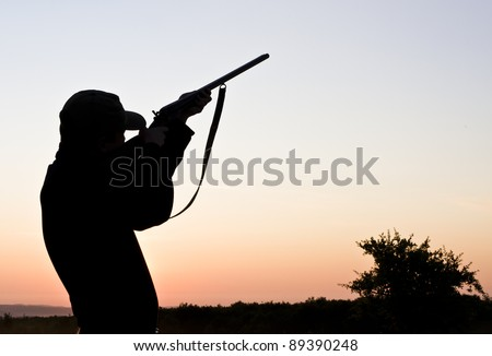 Silhouette of a young man shooting with a long rifle against sunset sky