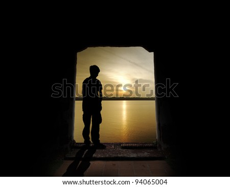 Silhouette of a young man standing at the opening of an ancient doorway to a surreal sunset off a tropical coast.