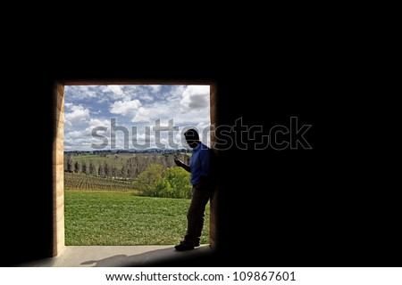 Silhouette of a young man using his mobile phone as he stands at the doorway to a green park with blue cloudy sky.