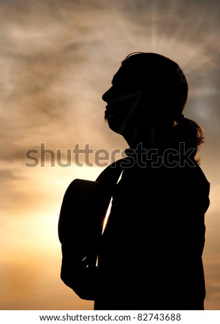 Silhouette of a young man with a ponytail gazing towards sky, holding his cowboy hat against his chest