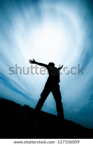 Silhouette of a young man with spread hands, shot against direct sun with lens flare, dramatic clouds background, saturated colors