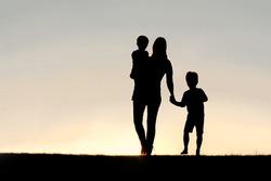 Silhouette of a young mother walking and lovingly holding hands with her happy little child, while holding his baby brother, outside in front of a sunset in the sky.