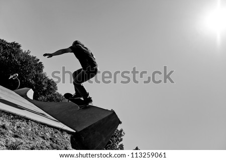 Silhouette of a young skateboarder doing a wall ride trick at the top of the ramp at a concrete skate park. Black and white with high contrast..