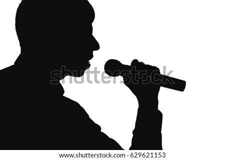 Silhouette of a young talented man who mastered the art of singing into a microphon