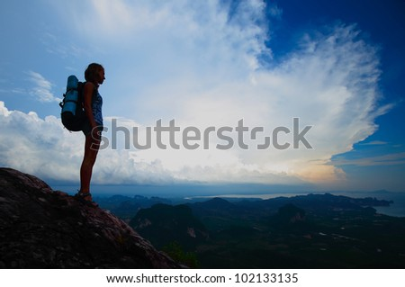 Silhouette of a young tourist with backpack standing on top of a mountain - stock photo