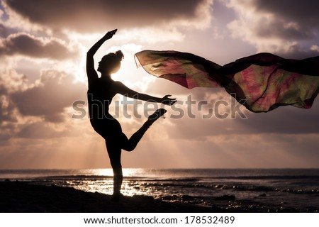 Silhouette of a young woman dancing at the beach with a tissue