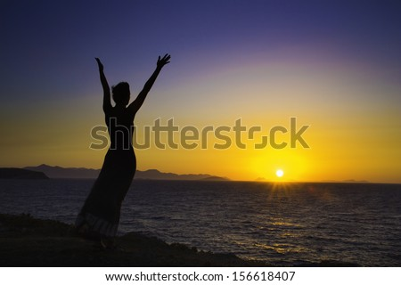 Silhouette of a young woman expressing joy at sunrise or sunset across an ocean towards islands. Bodrum, Turkey/ silhouette of woman feeling joy