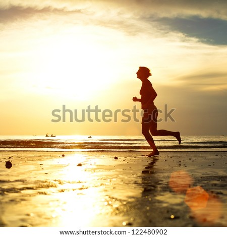 Silhouette of a young woman jogger at sunset on the seashore