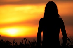 Silhouette of a young woman standing in dry grass field on sunset
