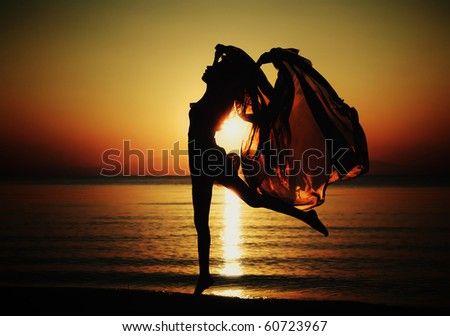 Silhouette of a young woman traveling in the rays of the rising sun. Horizontal photo