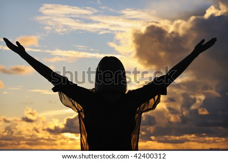 Silhouette of a young woman with outstretched hands against sunset sky - stock photo