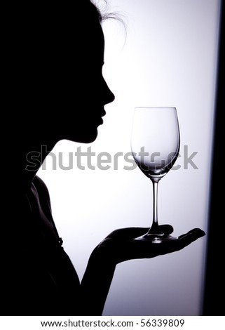 Silhouette of a young woman with vine glass