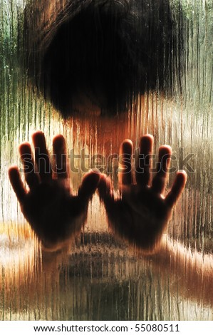 Silhouette of abused child behind the glass