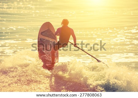 silhouette of active surfer on...