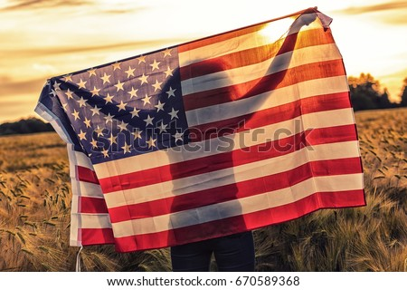 Silhouette of African American girl teenager female young woman in field of wheat or barley crops holding USA stars and stripes flag in golden sunset evening sunshine