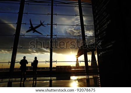 Silhouette of airline passengers in an airport lounge at the wide observation window watching an airplane flying of against a surreal sunset in the horizon with direction signage in the foreground. - stock photo