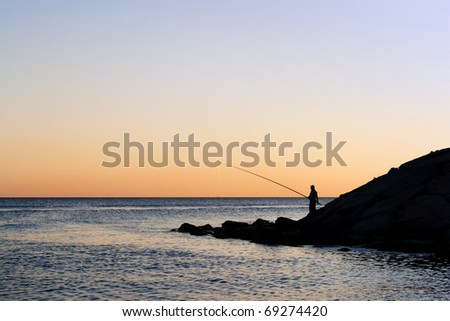 Silhouette of alone fisherman on sunset