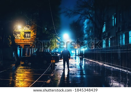 Silhouette of alone stranger in hood at night city street in rain. Creepy killer or stalker, criminal stands in shadow with urban lights reflected in puddles. Thriller horror mysterious atmosphere Сток-фото ©