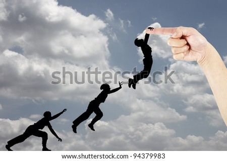 Silhouette of an active boy in motion jumping to catch hold of a female fingertip against a blue cloudy sky.